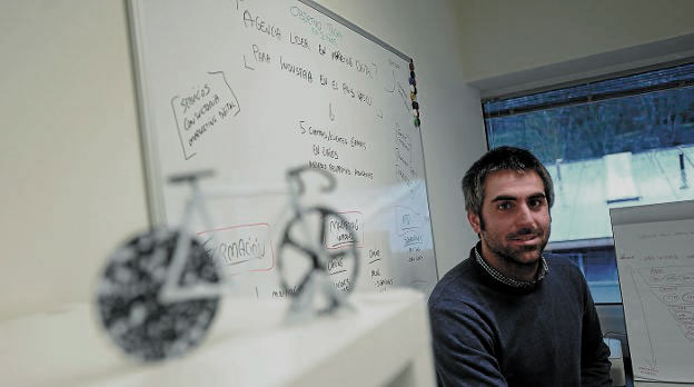 Man smiling into camera in front of a white board.