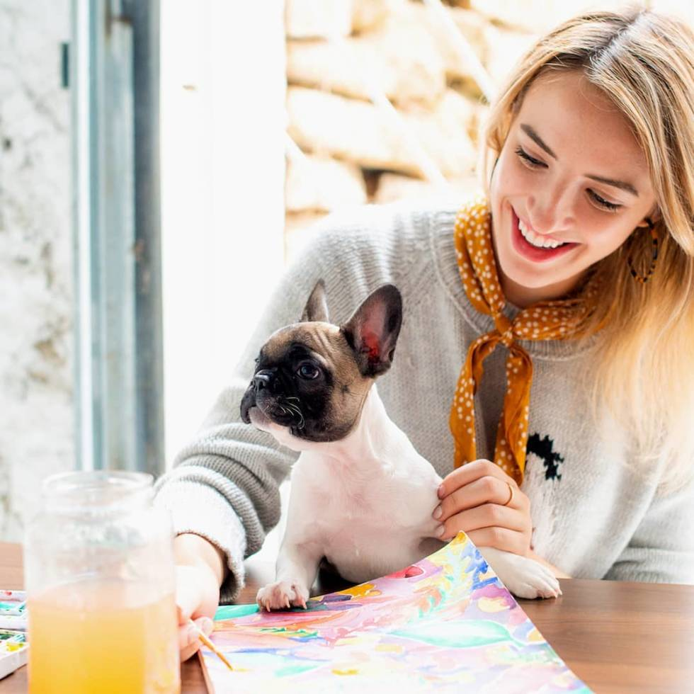 Woman holding a dog while watercolor painting.