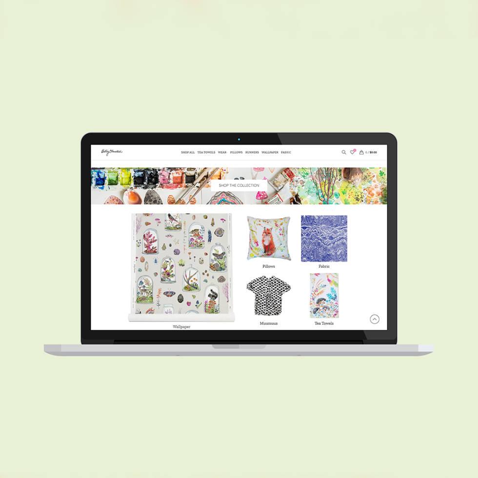 Macbook screen showing custom website design with e-commerce store