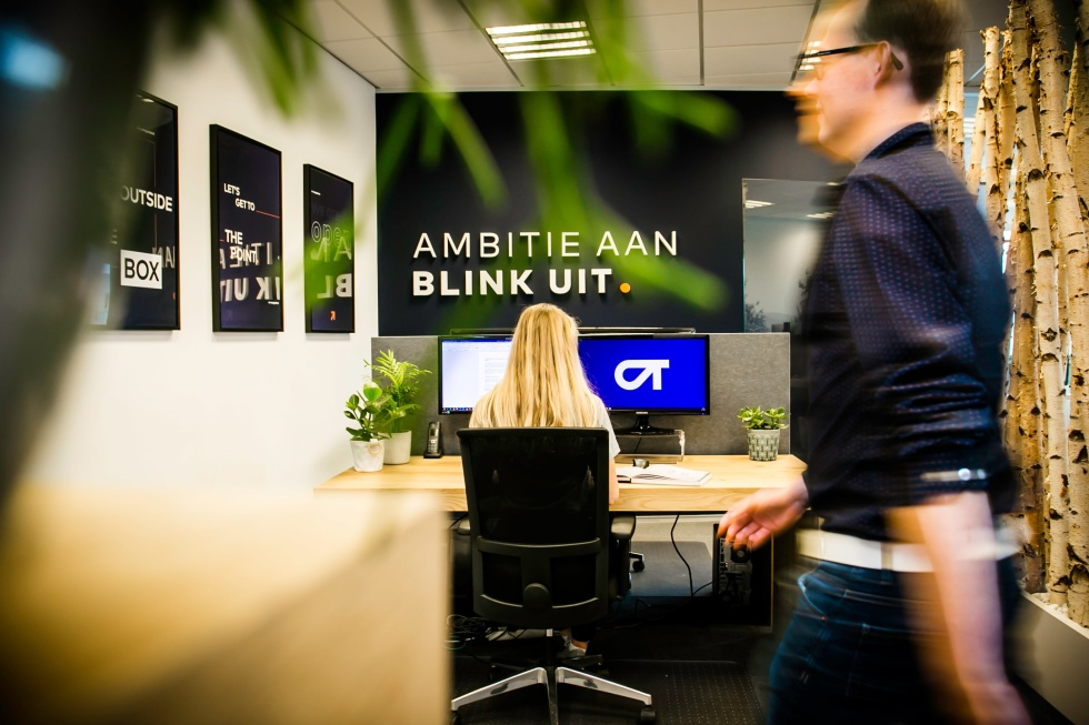 Image of a person walking by a desk and the text Ambitie aan blink uit.