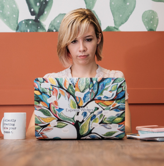 A photo of Julia McCoy sitting at a table with an open laptop in front of her.