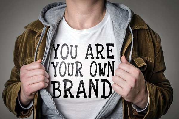 "Image of man pulling back a jacket to reveal a shirt that reads ""You Are Your Own Brand"""