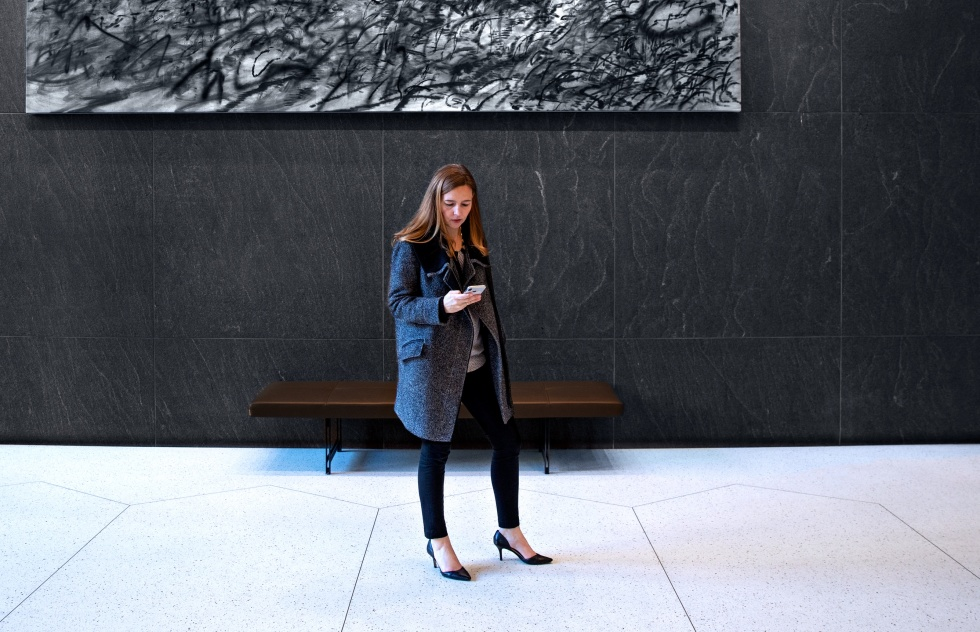 Image of UrbanSitter Co-Founder and Vice President of Marketing Daisy Downs looking at her phone