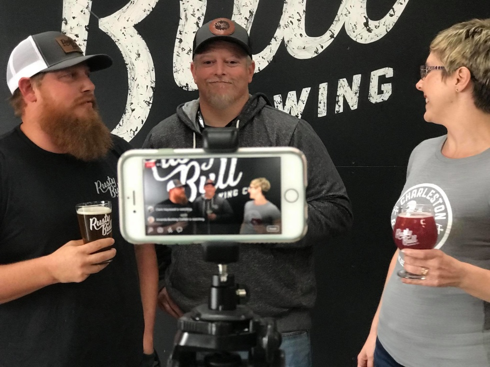 Two men and a woman holding beer in front of a phone doing a Facebook live broadcast.