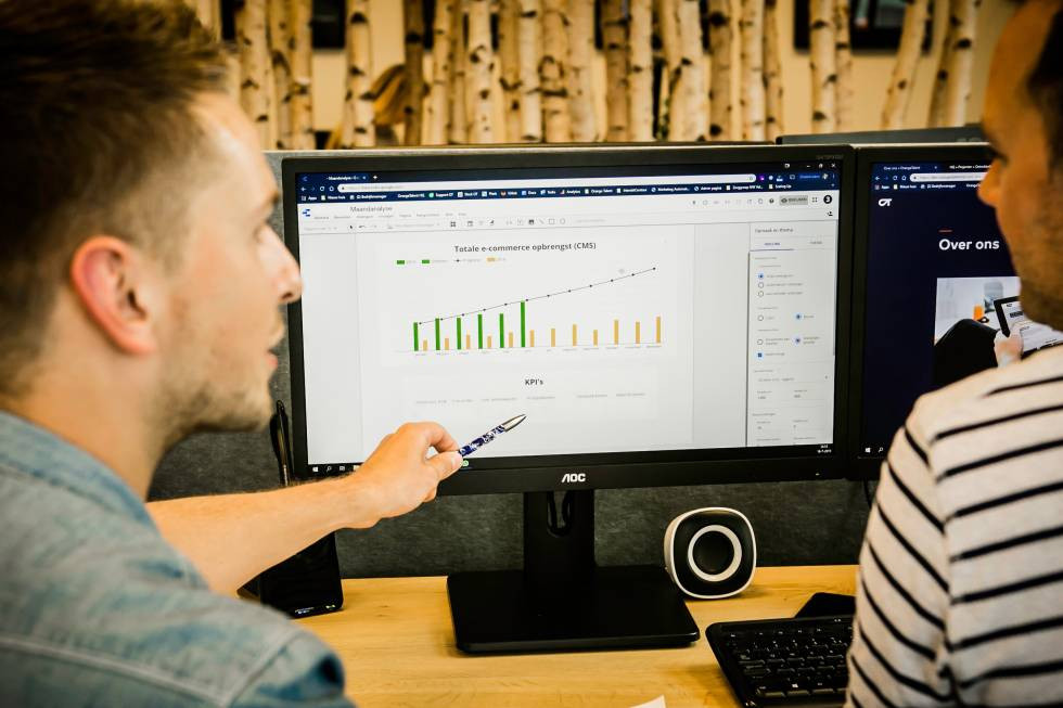 Image of two people looking at a computer monitor with a graph on it and one is pointing to the graph