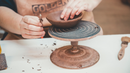 Close up of a ceramics artist at R. Wood studio forming a bowl with their hands.