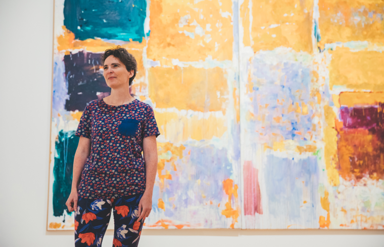 Hillary Brown smiles while standing in front of a large abstract painting.