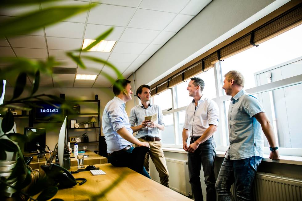 Image of 4 people talking next to a window