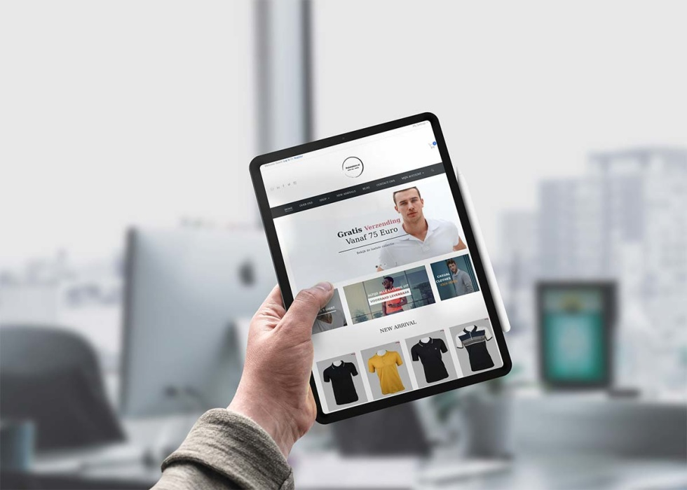 Photo of a hand holding a tablet that is displaying a clothing e-commerce site.