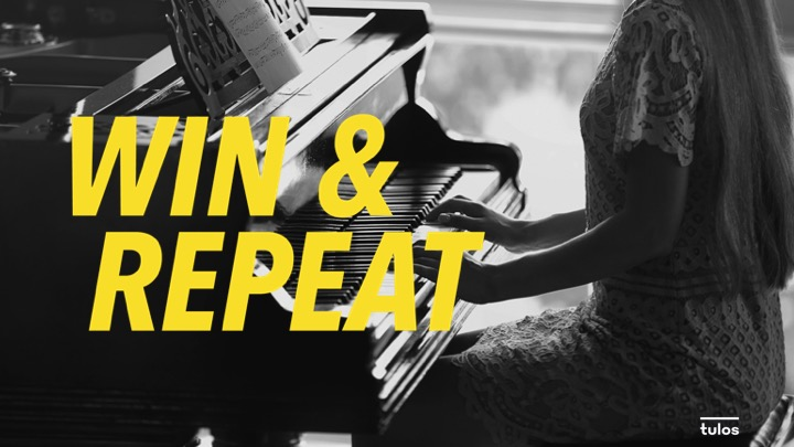 """Image of person playing piano with the words """"win & repeat"""" written"""