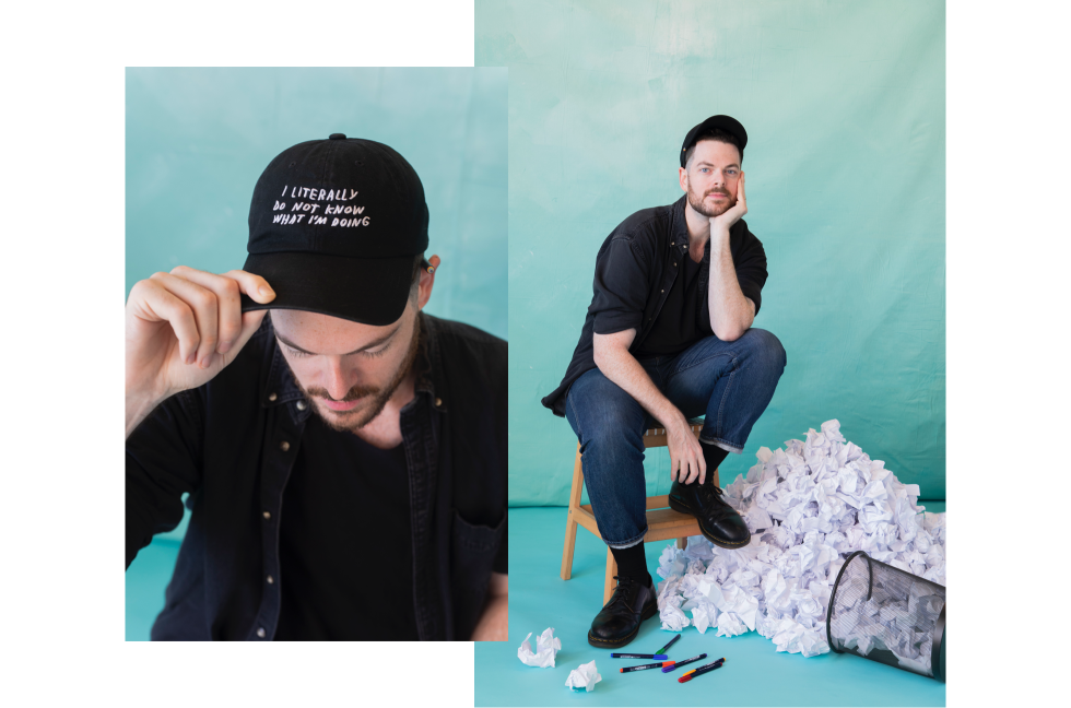 Adam Kurtz wearing a hat with his art and sitting on a stool next to tossed ideas.