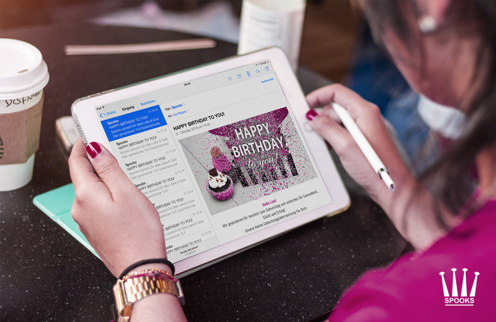 "Woman holding an iPad with an email that says ""Happy Birthday"""