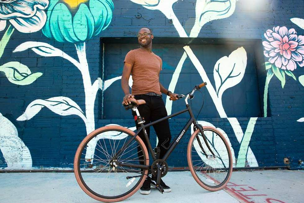 A Mailchimp employee standing with a bicycle