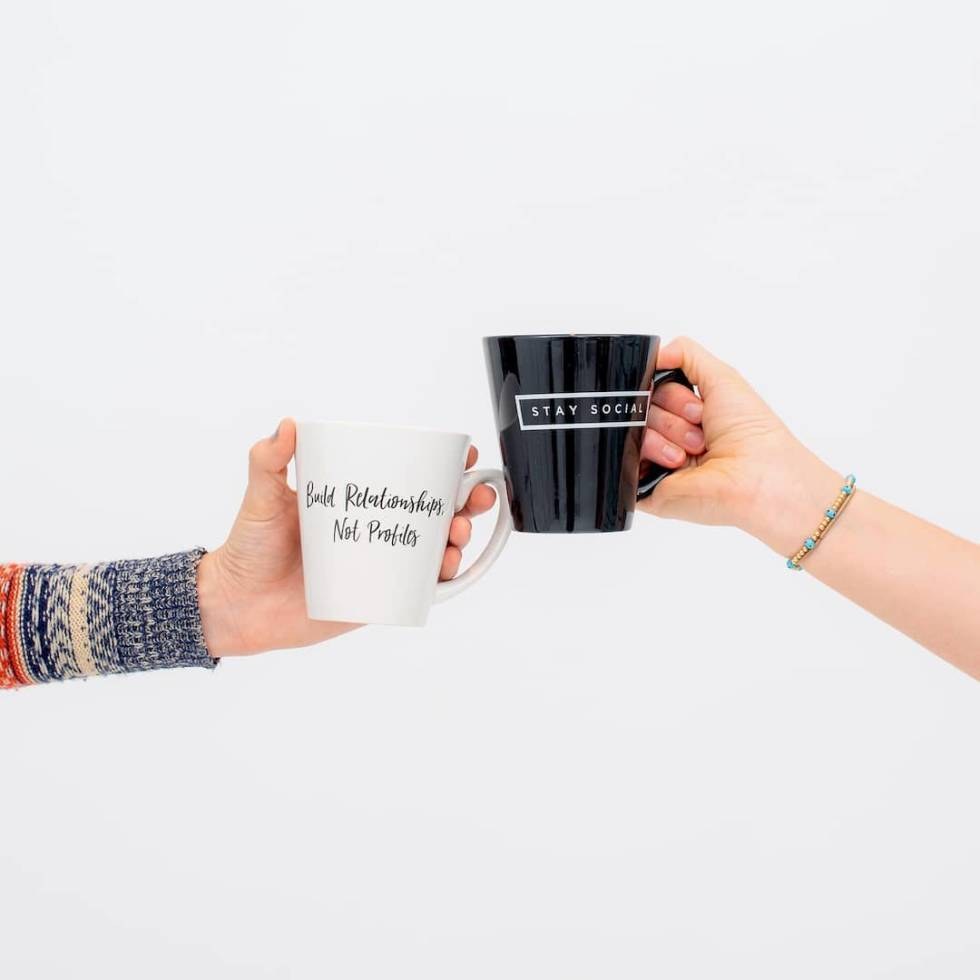 Image of two people holding coffee mugs