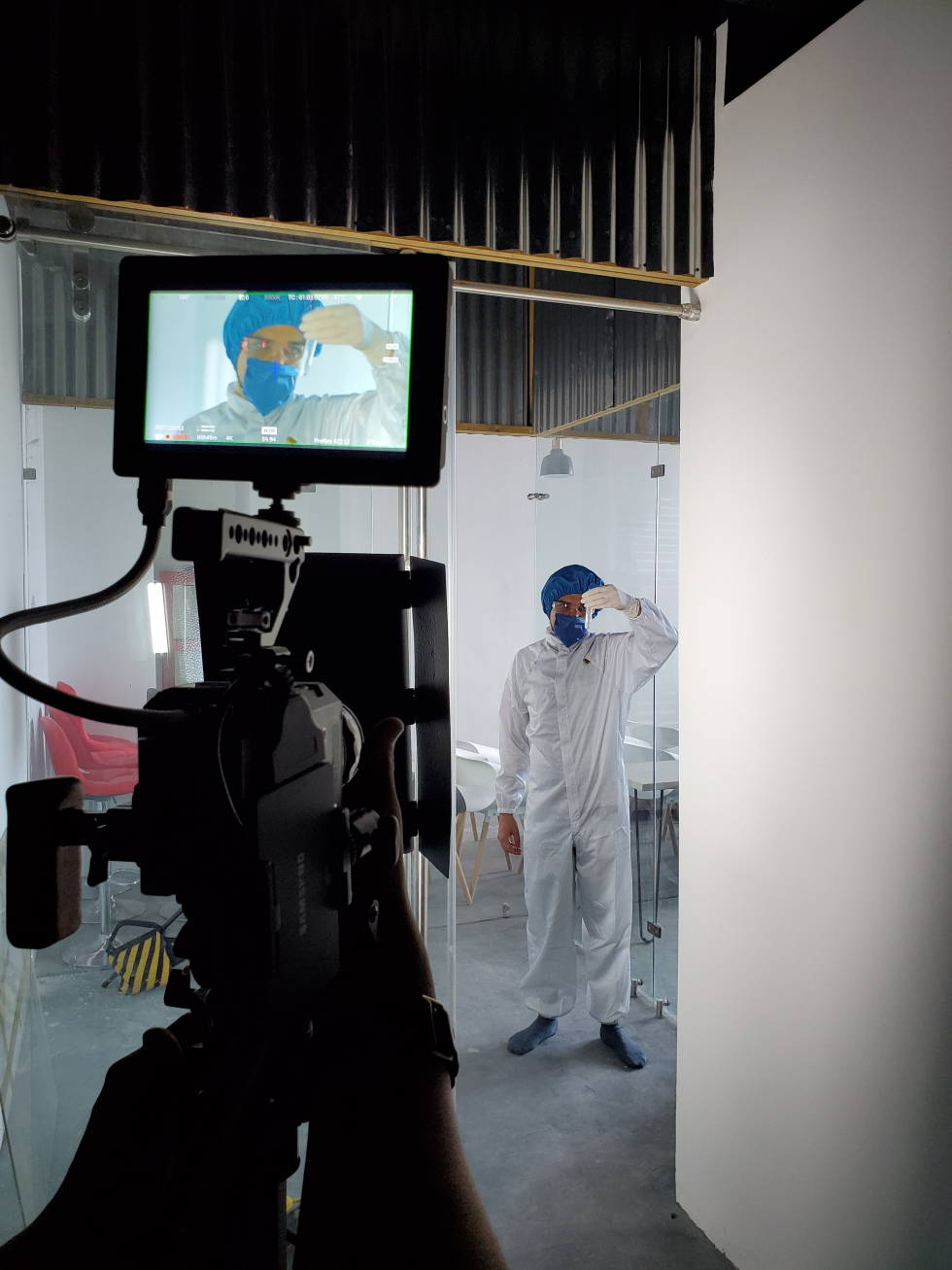 Image of a person in PPE gear in front of a camera