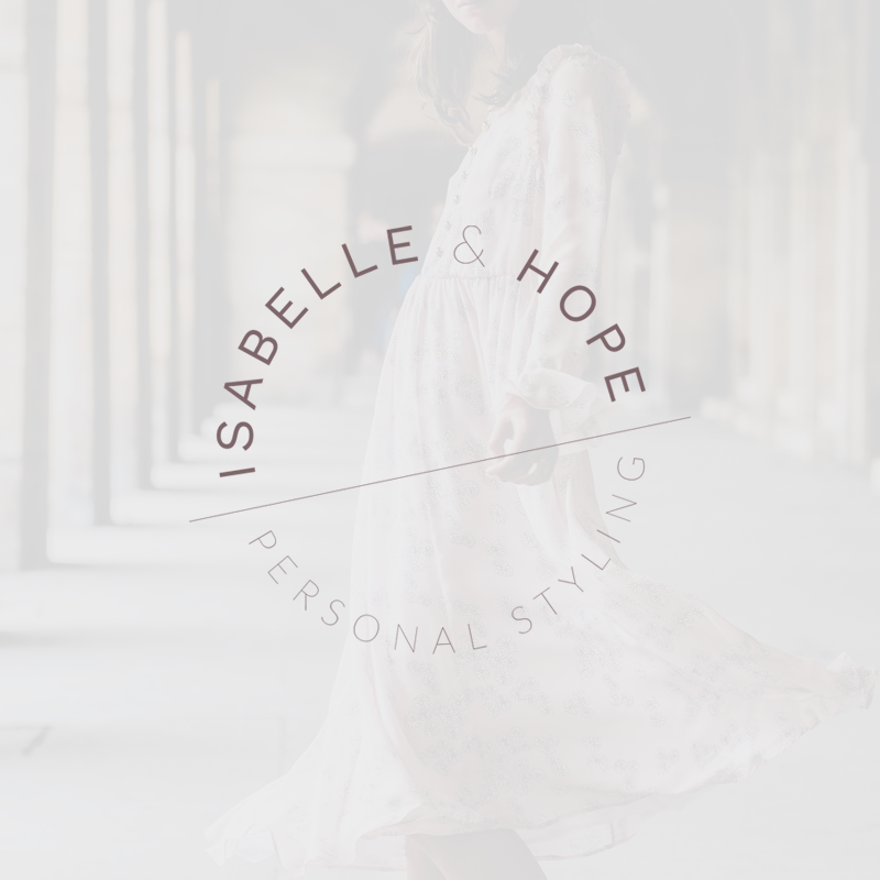 """Background image of woman in a decorative white dress in a long hallway that has been very faded. Text that says """"Isabelle & Hope / Personal Styling"""" overlays faded image and forms a circle."""