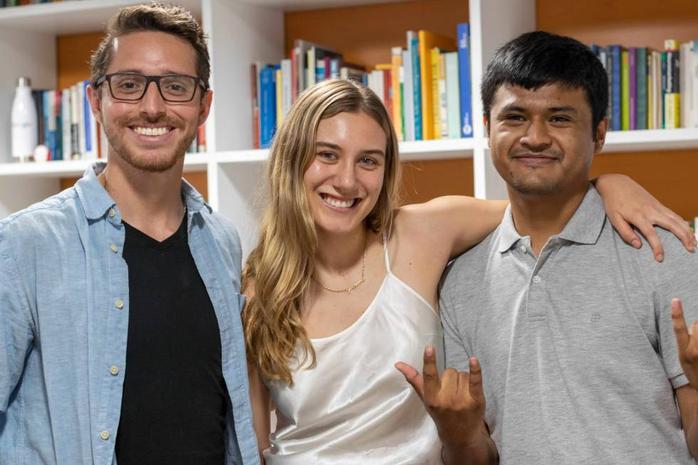 Image of 3 people smiling in front of a bookshelf