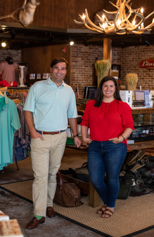 Founder TJ Callaway and Creative Director Virginia Johnson stand in their Buckhead Atlanta store. Both are standing and smiling at the camera. TJ wears a light blue polo and Virginia wears a bright red blouse.