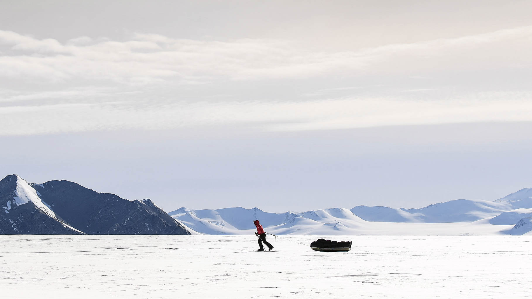 Person pulling sled across frozen tundra in front of mountains.