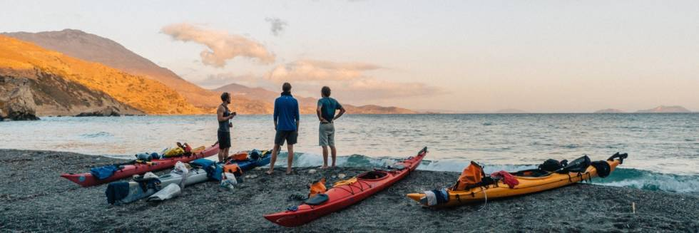 Image of three people standing next to kayaks on a beach.