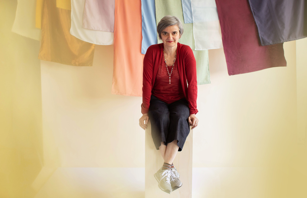 A photograph of a woman sitting on a stool in front of colorful linens.