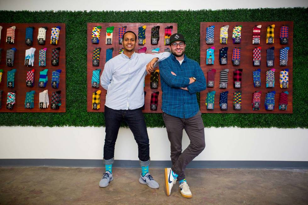 Stefan Lewinger and Futhum Tewolde of Sock Fancy smiling in front of a wall covered in socks.