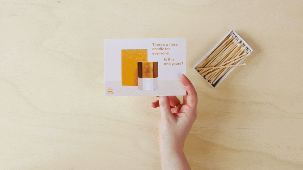 """A photo of a person's hand turning a postcard back and forth to show how the copy on both sides works together. Copy on front: """"There's a floral candle for everyone. Is this one yours?"""" Copy on back: """"Get your free candle"""""""