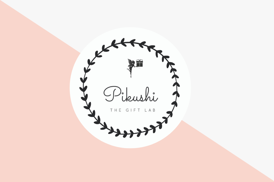 Logo design for Pikushi 'The Gift Lab.' Text sits in center of white circle on center of page. White circle with text has black decorative border. Circle sits on center of page against rectangle that's been split diagonally from top left corner to bottom right corner of page. Bottom half creates pink triangle against a light gray top half triangle.