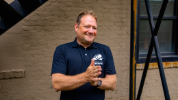Co-founder of Freshtix, Iain Bluett smiles while sporting a branded t-shirt outside of the Freshtix office.