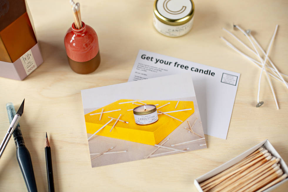 Postcards lying alongside a matchbox filled with matches and writing utensils