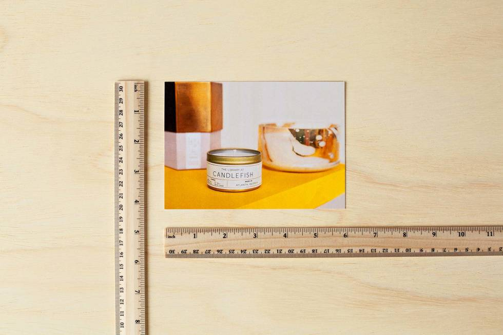 Photo of a postcard lined up against 2 rulers to show the dimensions