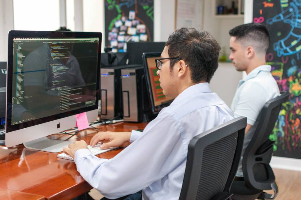 Image of two people sitting at desks working on their computers
