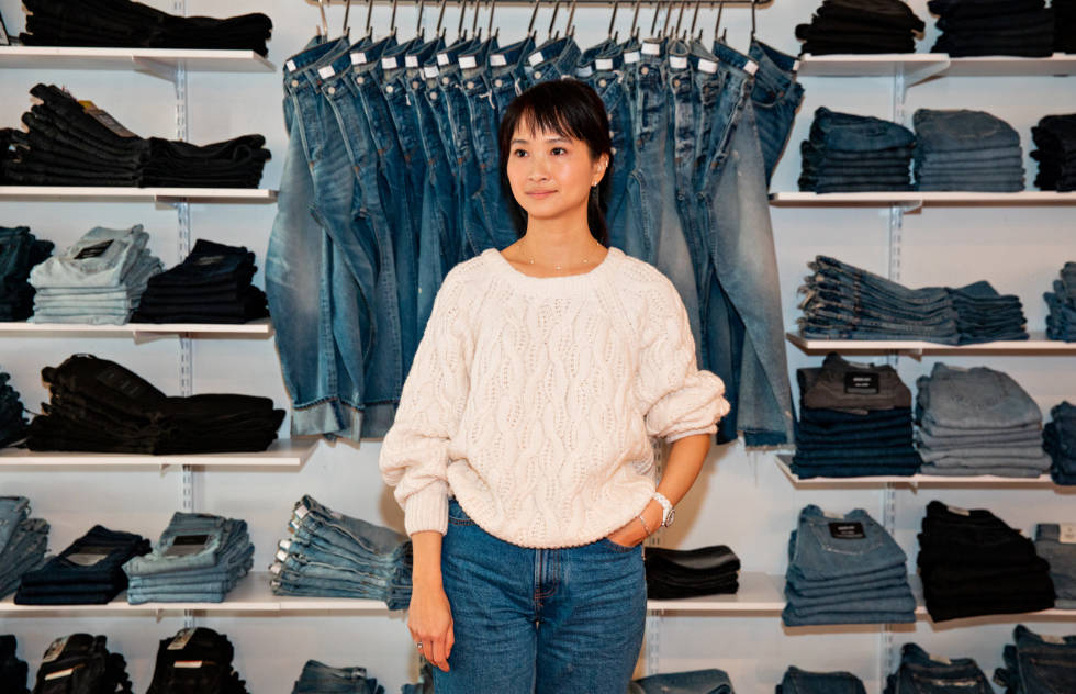 Co-owner of Azalea standing in front of a wall of merchandise.