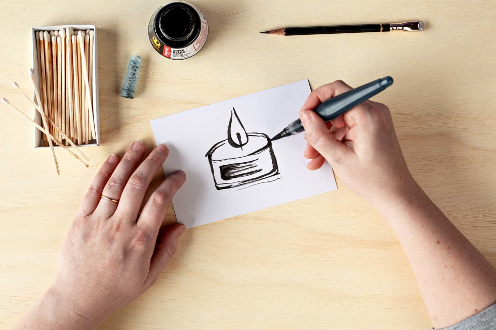 Photo of a person's hands drawing a picture of a candle with a marker