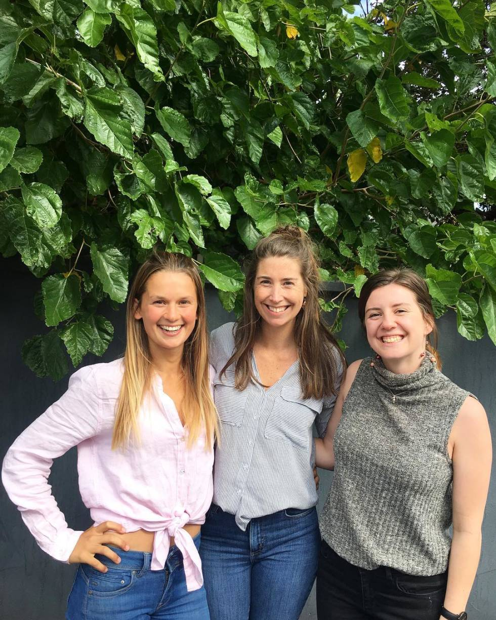 Three women smiling and posing together for a photo against green, vegetation background.