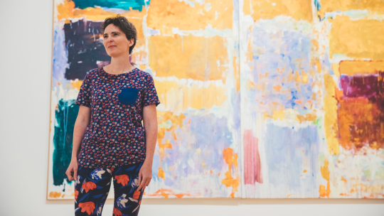 Hillary Brown stands in front of a large painting.