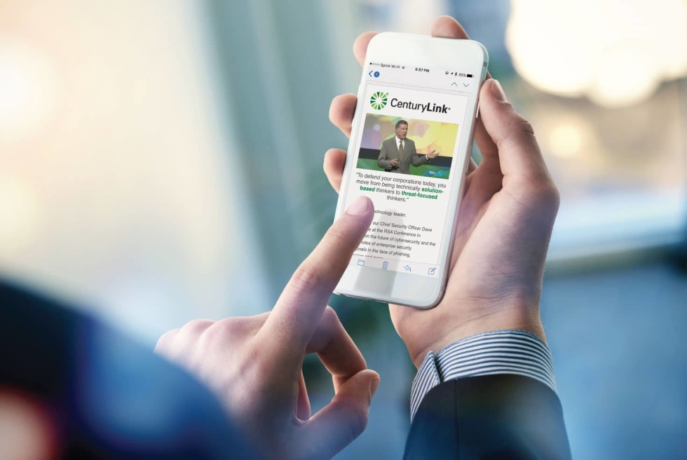 Man holding smart phone open to email newsletter. Template features logo, image header, and centered black and green text.