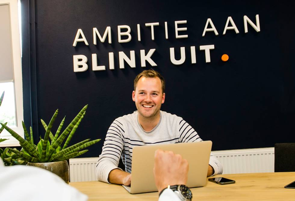 Image of a person at a  table with a laptop in front of them and the words Ambitie Aan Blink uit behind them.