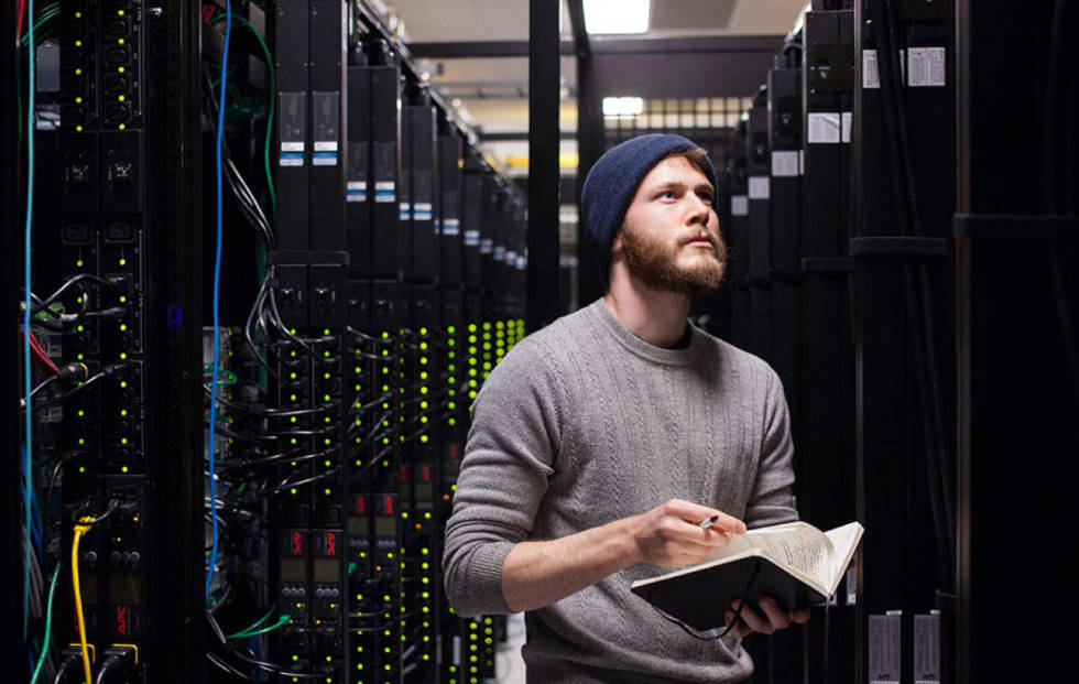 Someone looking at servers on a rack in a facility