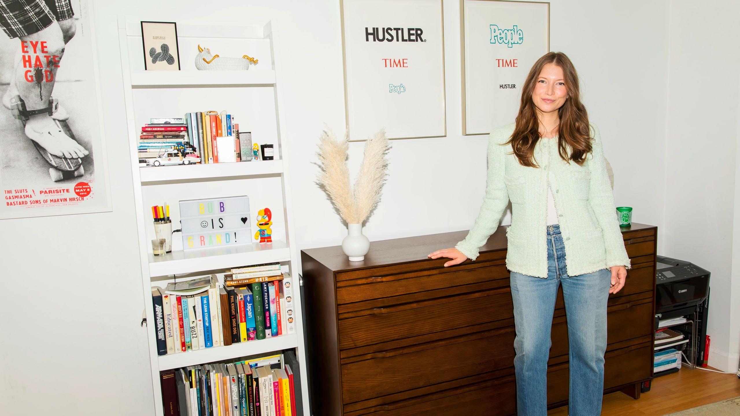 "Dianna Cohen stands in her bedroom in front of framed mastheads from ""People"" and ""Time"" magazines."