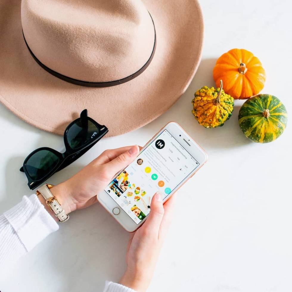 Image of a woman holding a phone next to a hat and small pumpkins.