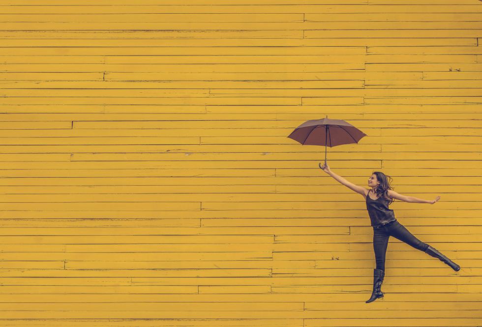 Image of person holding an umbrella with a yellow wall in the background