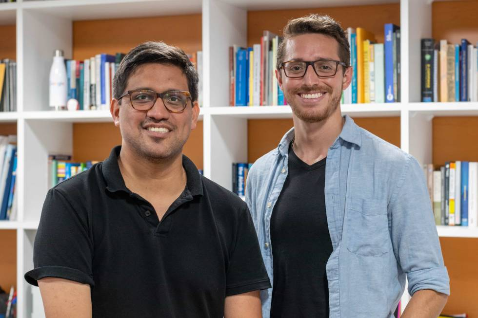 Image of two people in front of a bookshelf smiling