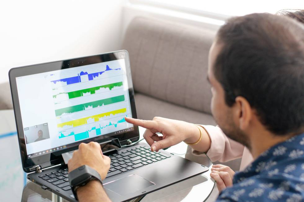 Image of a person in front of a laptop with graphs on it.