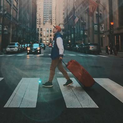 Man walking across the cross walk with a suitcase.