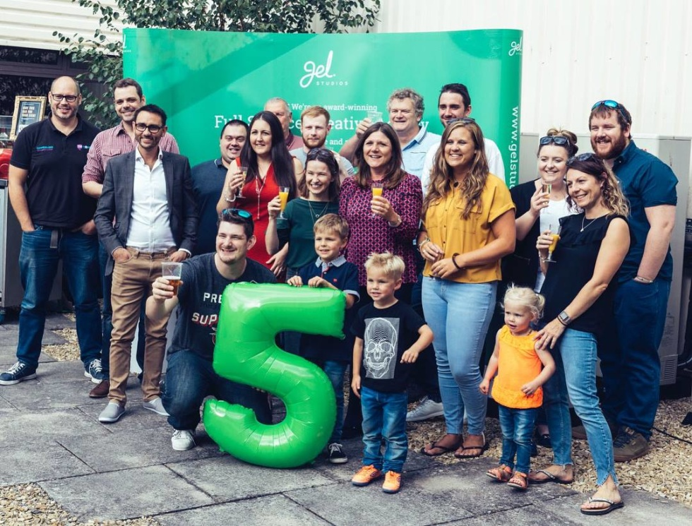 Photograph of employees standing in front of a large number 5 celebrating Gel Studios birthday