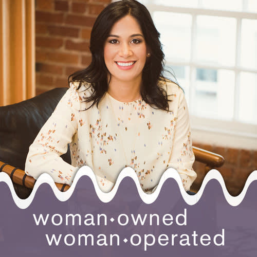 """Photo of woman sitting in chair and smiling at camera. Bottom one third of image has purple shape overlaying with white text reading, """"woman owned, woman operated"""""""