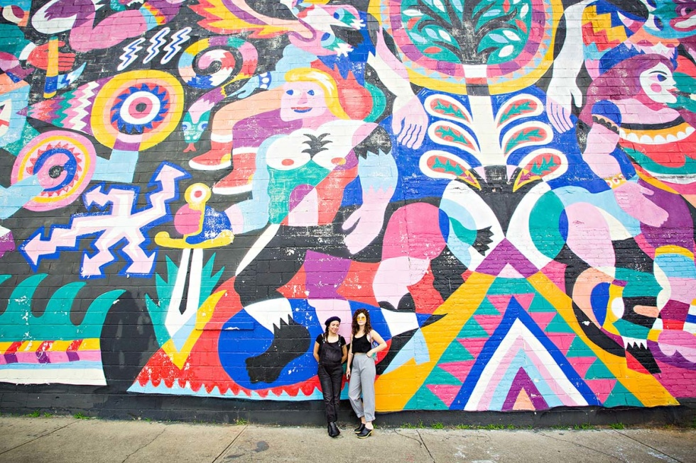 Two women standing in front an art wall