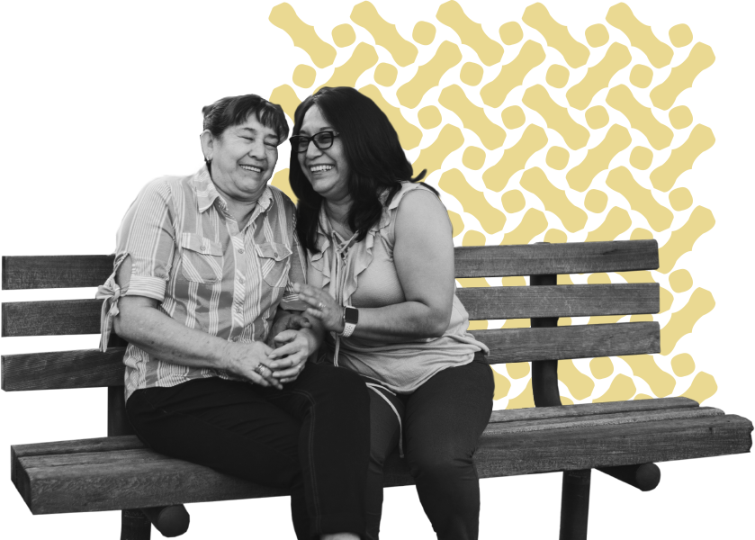 Two laughing women on a bench with a design of zig-zagging yellow bars behind them.