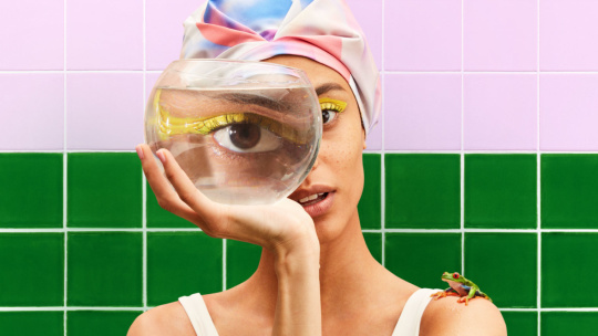 A woman peers through a fishbowl, but it feels like she's peering into your soul.